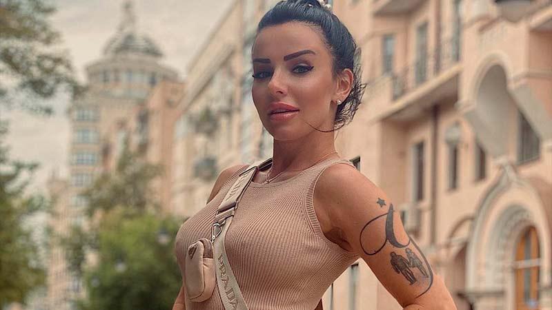 Yula volkova v platie, s pushkom na golove, s nakachennimi gubami i tatuagem smotrit v kameru
