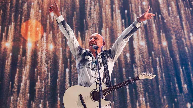 Denis Maidanov s gitaroy i rykami v storoni, ulibaetsia